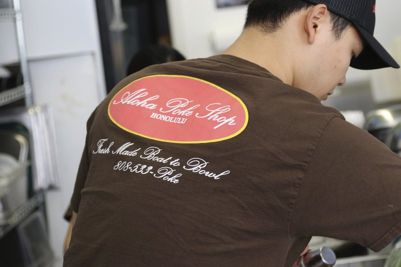 This Tuesday, April 16, 2019, photo shows Ryne Aniya preparing food before the lunch rush at Aloha Poke Shop, a store in Honolulu that received a letter from Chicago-based Aloha Poke Co. (AP Photo/Audrey McAvoy)