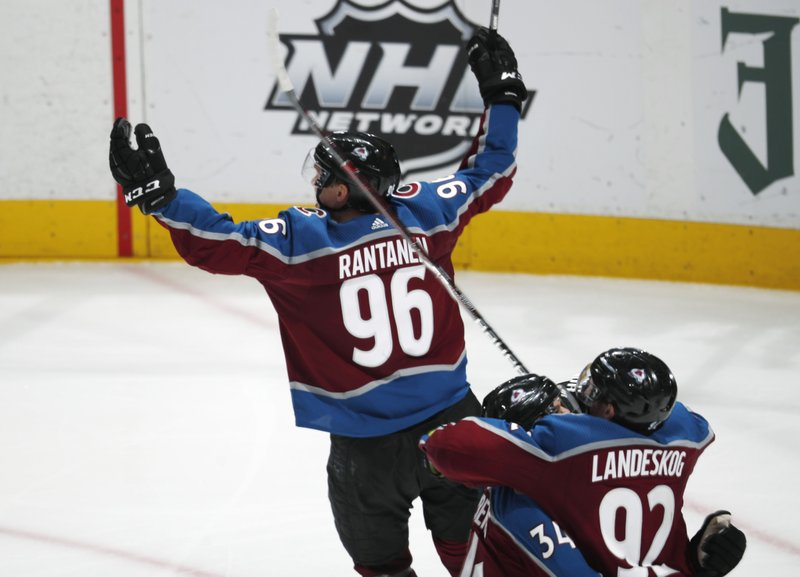 Colorado Avalanche right wing Mikko Rantanen (96) lifts up his arms in celebration after scoring in overtime against the Calgary Flames during Game 4 of an NHL hockey playoff series Wednesday, April 17, 2019, in Denver. (92) hugs Carl Soderberg (34). The Avalanche won 3-2. (AP Photo/David Zalubowski)