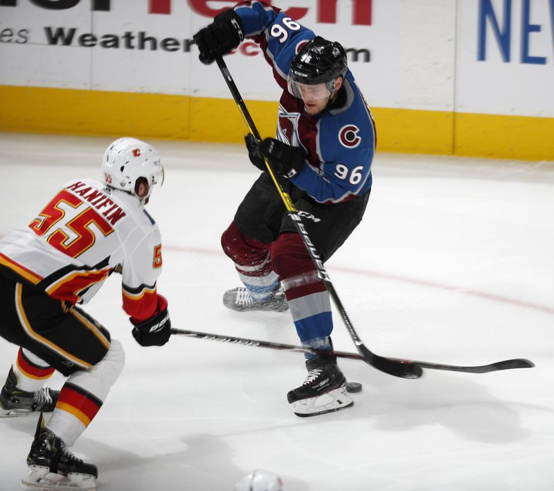 Calgary Flames defenseman Noah Hanifin, left, pokes the puck away from Colorado Avalanche right wing Mikko Rantanen during the first period of Game 4 of an NHL hockey playoff series Wednesday, April 17, 2019, in Denver. (AP Photo/David Zalubowski)