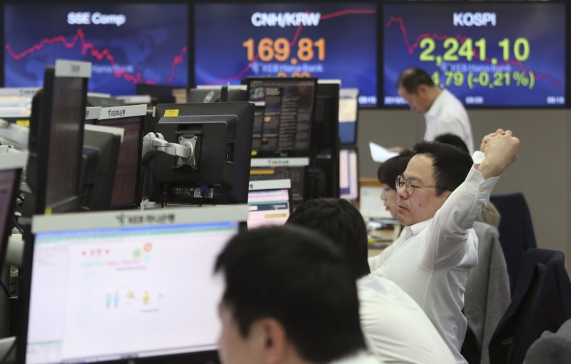 A currency trader stretches at the foreign exchange dealing room of the KEB Hana Bank headquarters in Seoul, South Korea, Thursday, April 18, 2019. (AP Photo/Ahn Young-joon)