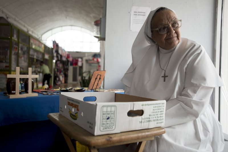 Sister Carmen Negrón, 64, sells handmade rosaries and religious icons in the Plaza del Mercado in San Juan, Puerto Rico, Wednesday, April 17, 2019. (AP Photo/Carlos Giusti)