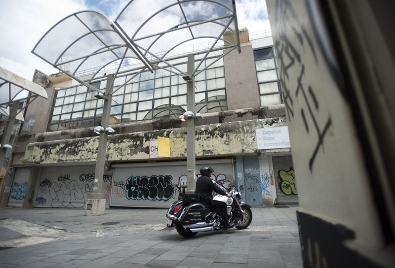 A municipal police officer drives past shuttered shops in the Paseo de Diego of San Juan, Puerto Rico, Wednesday, April 17, 2019. (AP Photo/Carlos Giusti)