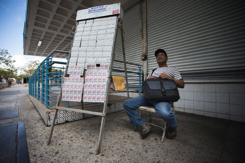 Lottery vendor Manuel Almonte waits for customers in the sparce Rio Piedras area of San Juan, Puerto Rico, Wednesday, April 17, 2019. (AP Photo/Carlos Giusti)