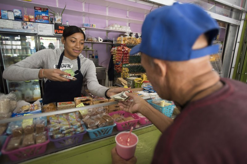 Genesis Perez Martinez, 24, works at the Plaza del Mercado in the Rio Piedras area of San Juan, Puerto Rico, Wednesday, April 17, 2019. (AP Photo/Carlos Giusti)