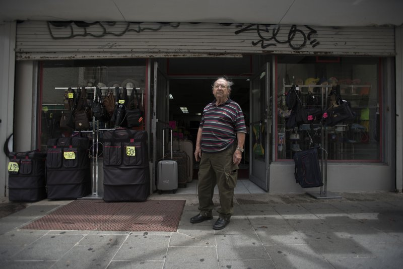 Luggage seller Jose Forteza, 88, poses for a portrait outside his store, one of the few still open in the Paseo de Diego of San Juan, Puerto Rico, Wednesday, April 17, 2019. (AP Photo/Carlos Giusti)