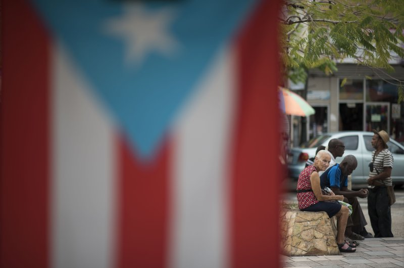 Residents sit outside the Plaza del Mercado in the Rio Piedras area of San Juan, Puerto Rico, Wednesday, April 17, 2019, where a Puerto Rican flag hangs. (AP Photo/Carlos Giusti)