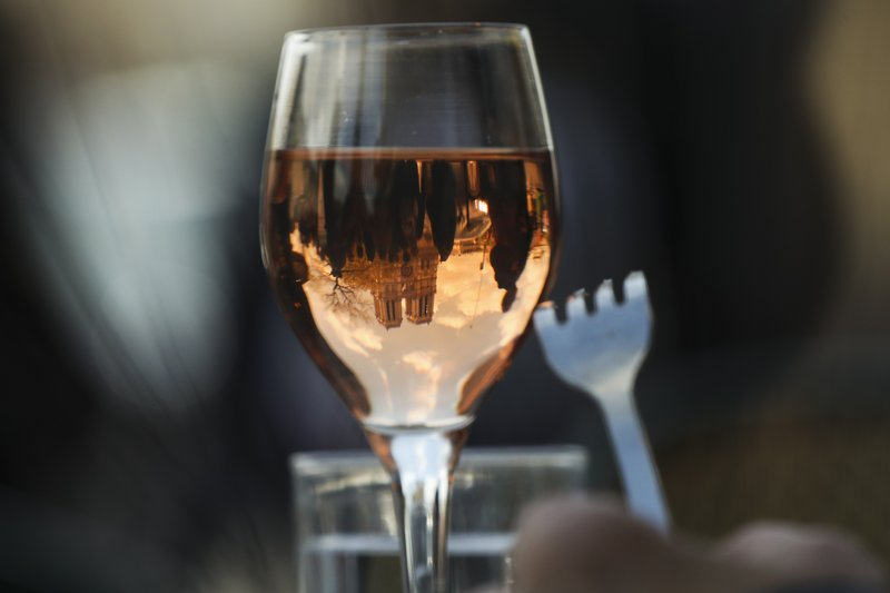 The Notre Dame Cathedral is reflected in a wine glass as a customer eats nearby the cathedral in Paris, Wednesday, April 17, 2019. (AP Photo/Francisco Seco)