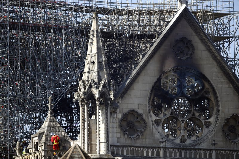 A fire fighter makes his way on a balcony of Notre Dame cathedral Wednesday, April 17, 2019 in Paris. (AP Photo/Francois Mori)