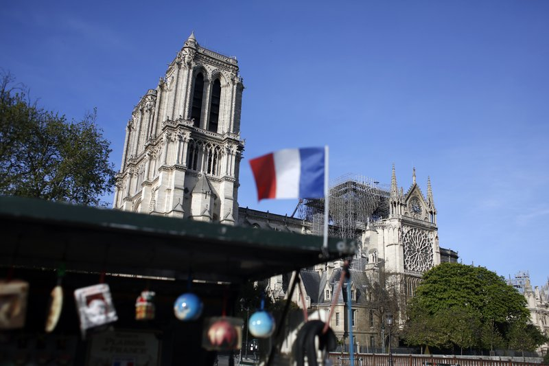 A French flag flaps in front of Notre Dame cathedral, in Paris, Wednesday, April 17, 2019. Notre Dame Cathedral would have been completely burned to the ground in a