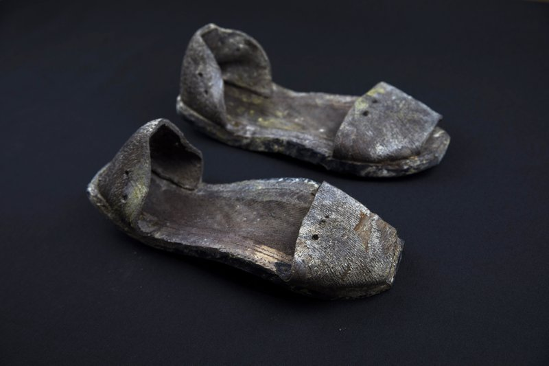 In this Thursday, March 26, 2019 photo, a pair of shoes are seen photographed after being exhumed from the scene of a mass grave at the cemetery of Paterna, near Valencia, Spain, as archaeologists conduct forensic analysis of the remains. (AP Photo/Emilio Morenatti)