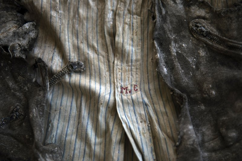 In this Thursday, March 26, 2019 photo, the clothes of a victim with monogram 'MG' embroidered into the shirt, photographed after the body was exhumed from a mass grave at the cemetery of Paterna, near Valencia, Spain, after archaeologists in Spain unearthed layers of human bones last year. (AP Photo/Emilio Morenatti)