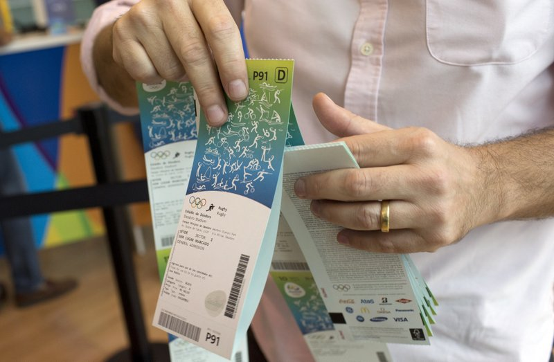 FILE - In this June 20, 2016, file photo, a man handles the Olympic tickets he just purchased at a shopping mall in Rio de Janeiro, Brazil. (AP Photo/Silvia Izquierdo, File)
