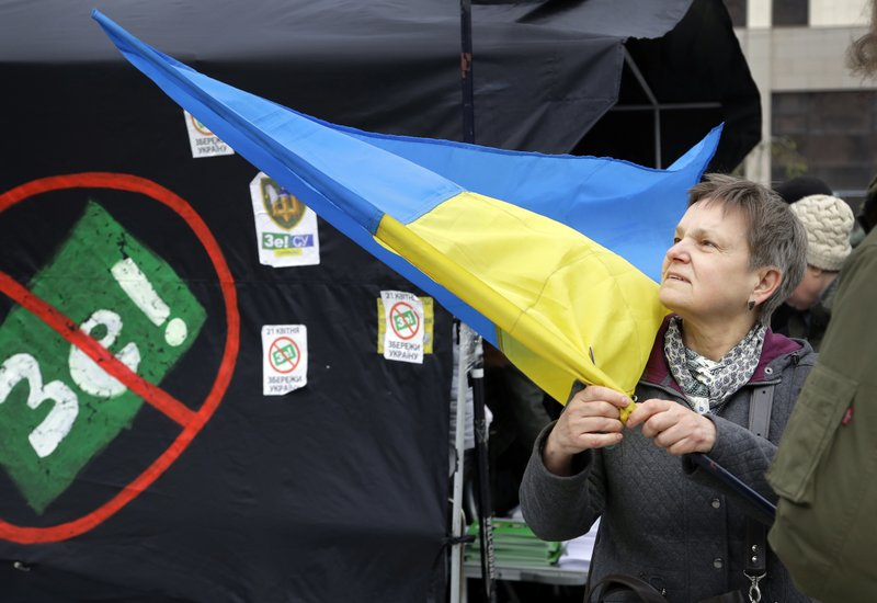 A woman holds an Ukrainian flag standing next to a tent of opponents of comedian and presidential candidate Volodymyr Zelenskiy in downtown Kiev, Ukraine, Wednesday, April 17, 2019. (AP Photo/Sergei Grits)