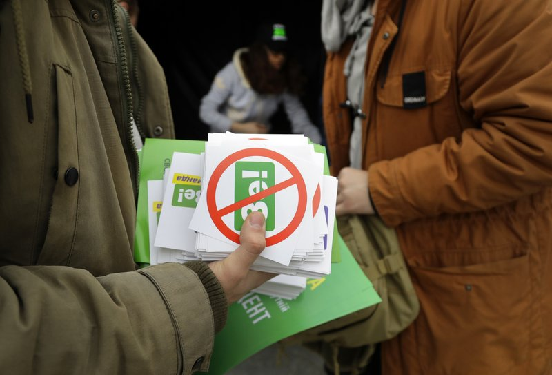 Opponents of Ukrainian comedian and presidential candidate Volodymyr Zelenskiy prepare to distribute stickers in downtown Kiev, Ukraine, Wednesday, April 17, 2019. (AP Photo/Sergei Grits)