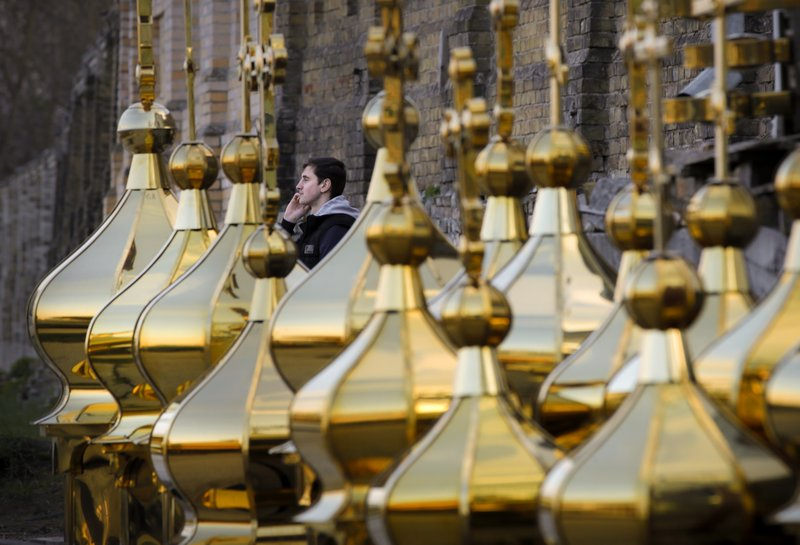 A youngster speaks on a cellphone sitting behind church construction elements for sale in Kiev, Ukraine, Wednesday, April 17, 2019. (AP Photo/Vadim Ghirda)