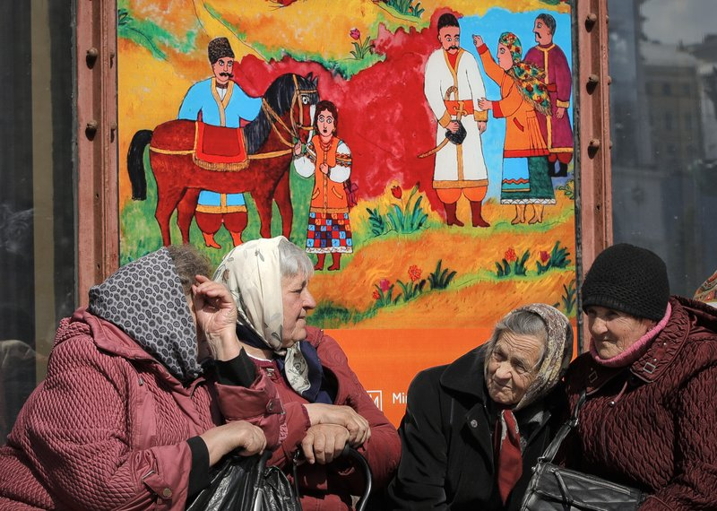 People sit on a sunny morning in Kiev, Ukraine, Thursday, April 18, 2019. The second round of presidential vote in Ukraine will take place on Sunday April 21. (AP Photo/Vadim Ghirda)