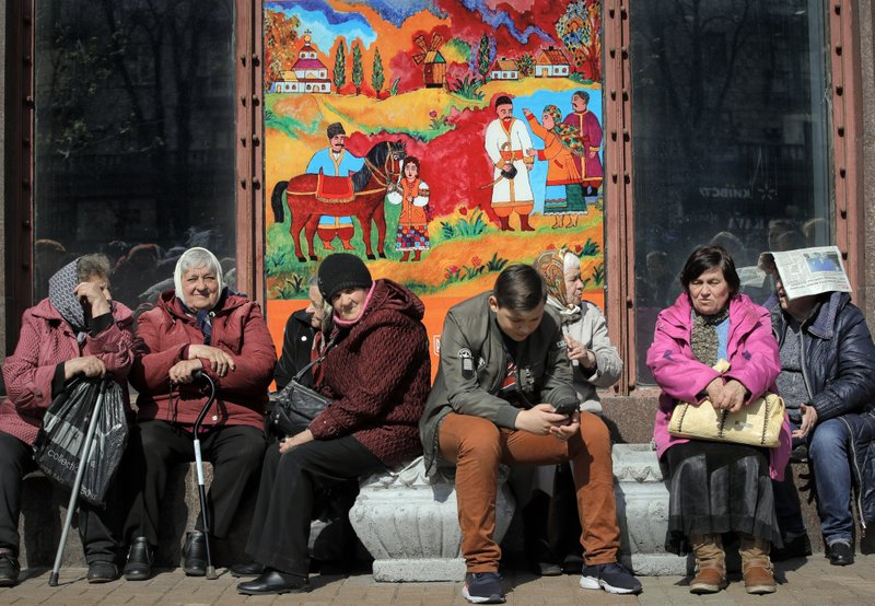 People sit on a sunny morning in Kiev, Ukraine, Thursday, April 18, 2019. The second round of presidential voting in Ukraine will take place on upcoming Sunday April 21. (AP Photo/Vadim Ghirda)