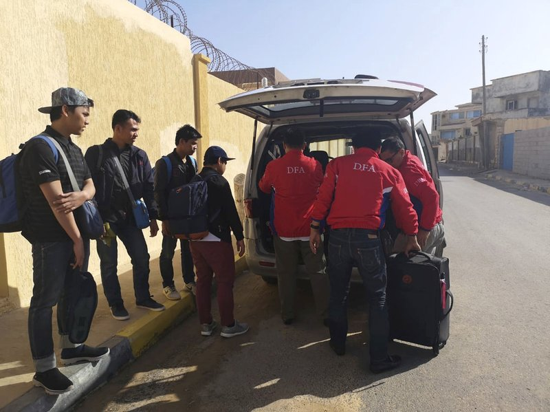 In this Wednesday, April 17, 2019, photo released by the Department of Foreign Affairs, Filipinos are assisted by staff of the department as they are evacuated from Tripoli, Libya. (Department of Foreign Affairs via AP)