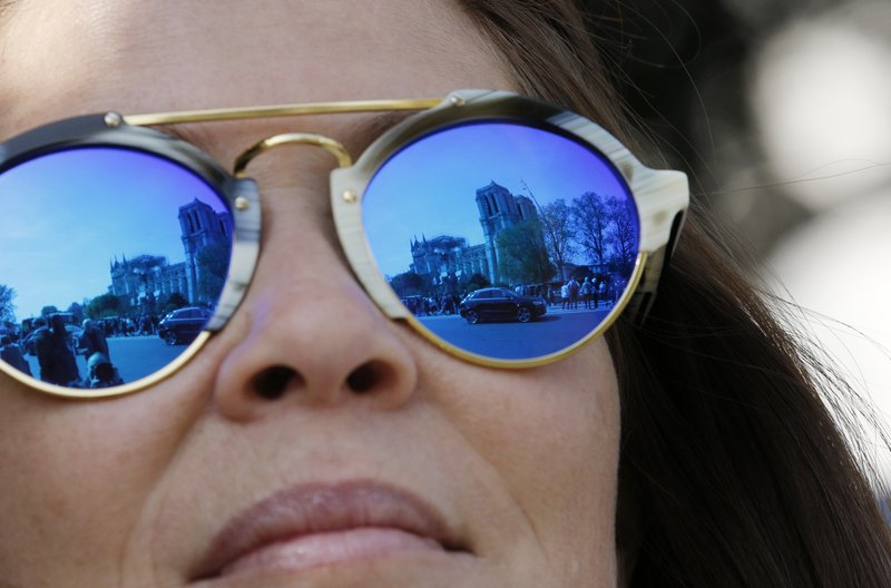 The Notre Dame Cathedral is reflected in the sunglasses of an onlooker in Paris, Thursday, April 18, 2019. (AP Photo/Christophe Ena)