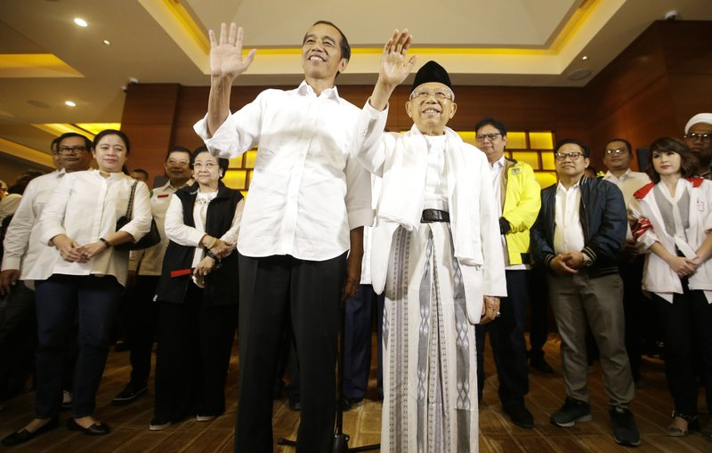 Indonesian President Joko Widodo, left, and his running mate Ma'ruf Amin wave to journalists after a press conference in Jakarta, Indonesia, Wednesday, April 17, 2019. (AP Photo/Achmad Ibrahim)