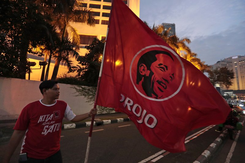 A supporter holds a flag bearing an image of Indonesian President Joko Widodo in Jakarta, Indonesia, Wednesday, April 17, 2019. (AP Photo/Dita Alangkara)