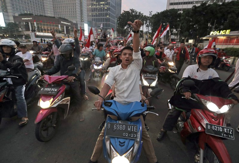 Supporters of Indonesian President Joko Widodo celebrate during a rally in Jakarta, Indonesia, Wednesday, April 17, 2019. (AP Photo/Dita Alangkara)