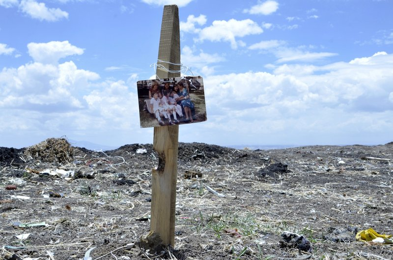 A photo hangs at the crash site for crash victims as Ethiopians hold the 40th day remembrance, as per Ethiopian tradition, in Bishoftu, Ethiopia, Thursday, April 18, 2019. (AP Photo/Samuel Habtab)