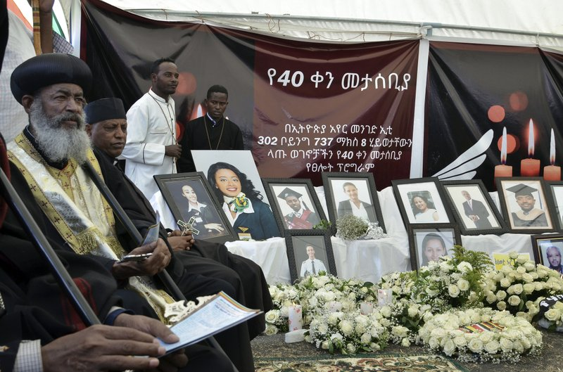 An Ethiopian priest pray as photos of the plane crash victims are displayed during the 40th day remembrance, as per Ethiopian tradition, in Bishoftu, Ethiopia, Thursday, April 18, 2019. (AP Photo/Samuel Habtab)
