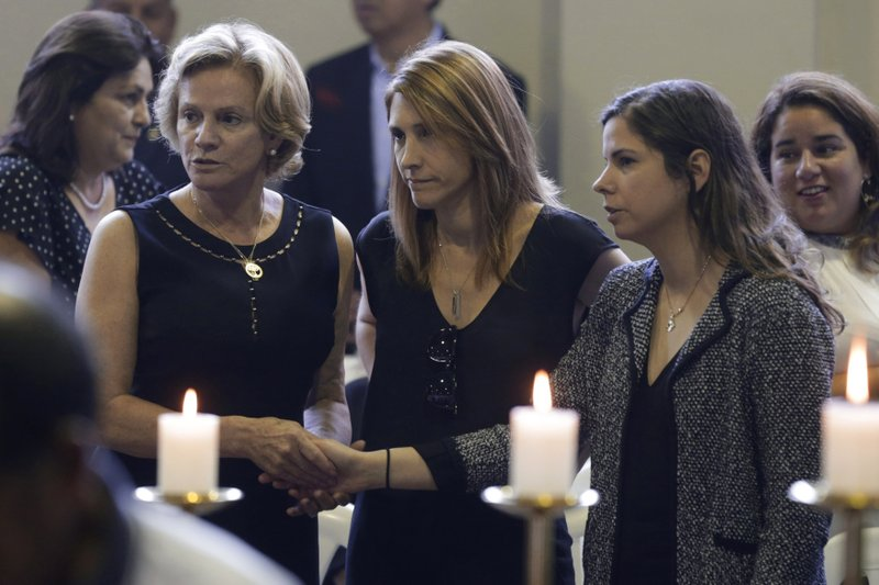 Pilar Nores, ex-wife of Peru's late President Alan Garcia, left, and their daughters, Josefina, center, and Luciana attend Garcia's wake at his party's headquarters in Lima, Peru, Thursday, April 18, 2019. (AP Photo/Martin Mejia)