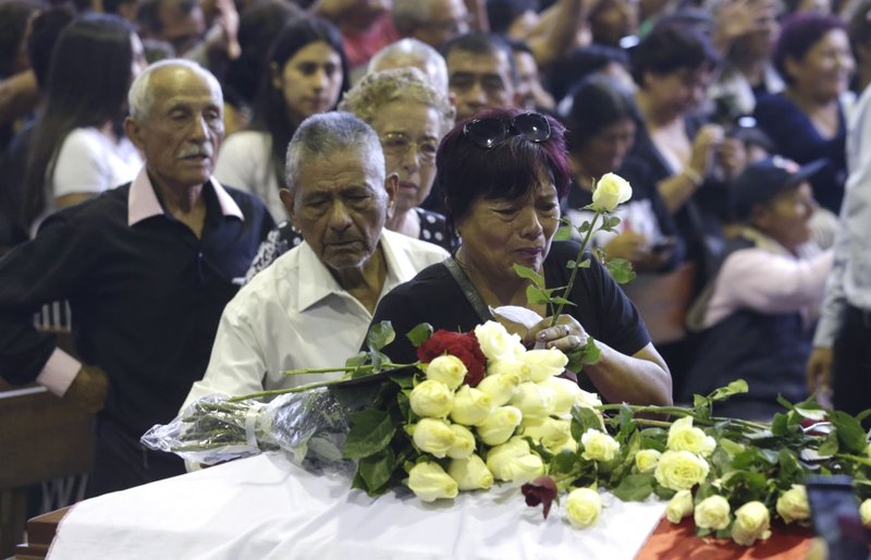 A supporter of Peru's late President Alan Garcia puts a flower on his coffin on the second day of his wake at his party's headquarters in Lima, Peru, Thursday, April 18, 2019. (AP Photo/Martin Mejia)