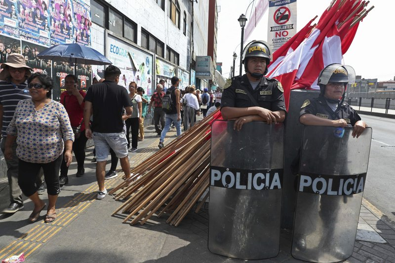 Police stand guard as people walk in a line to attend the wake of Peru's late President Alan Garcia at his political party's headquarters in Lima, Peru, Thursday, April 18, 2019. (AP Photo/Martin Mejia)