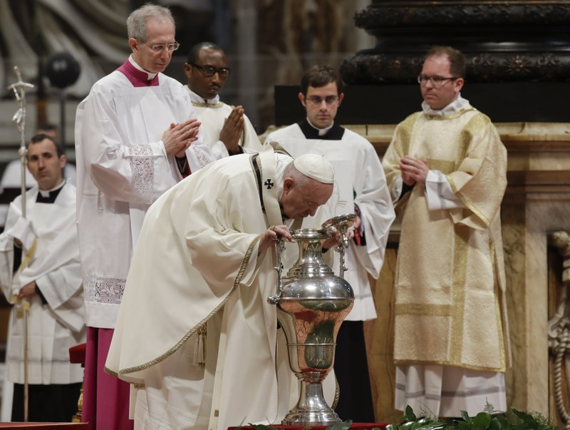 Pope Francis blows inside an amphora containing holy oil during a Chrism Mass inside St. Peter's Basilica, at the Vatican, Thursday, April 18, 2019. (AP Photo/Alessandra Tarantino)