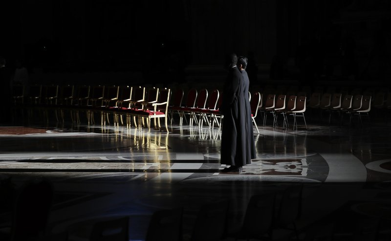 Two priests stand inside St. Peter's Basilica, at the Vatican,Thursday, April 18, 2019. (AP Photo/Alessandra Tarantino)