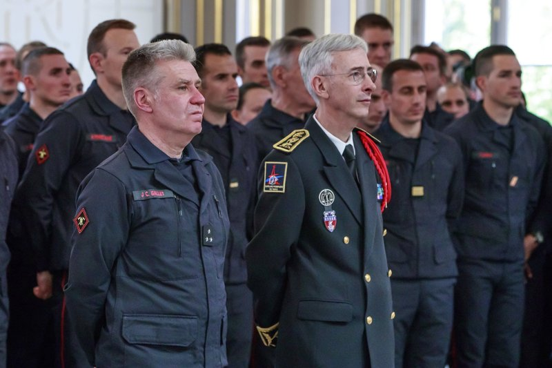 French General Jean-Claude Gallet, left, and Paris Prefect Didier Lallement listen to French President Emmanuel Macron addressing Paris Firefighters' brigade and security forces who took part at the fire extinguishing operations of the Notre Dame of Paris Cathedral fire, at the Elysee Palace in Paris, Thursday, April 18, 2019. (Christophe Petit Tesson, Pool via AP)