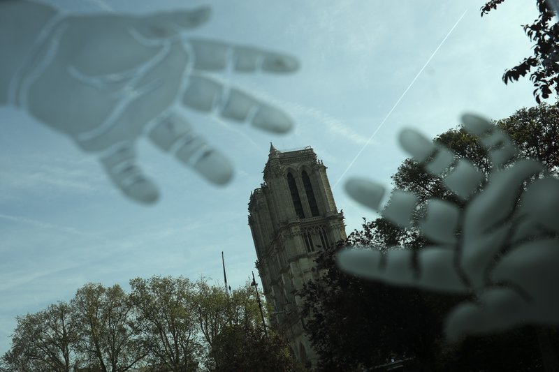Towers of the Notre Dame cathedral are seen through an engraved glass in Paris, Thursday, April 18, 2019. (AP Photo/Francisco Seco)