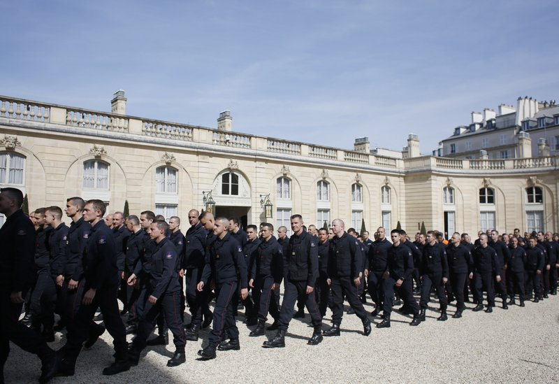 Emergency service personnel walk at the Elysee Palace in Paris after a meeting with French President Emmanuel Macron, Thursday, April 18, 2019. (AP Photo/Thibault Camus)