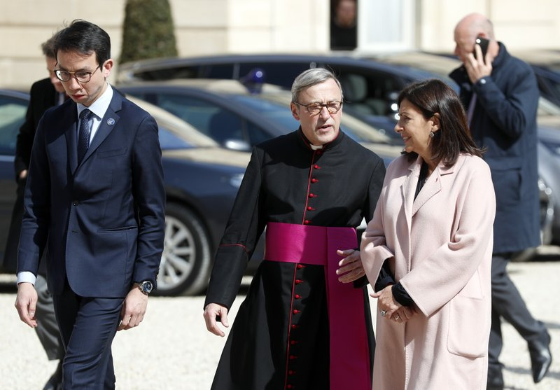 Rector of the Notre Dame Patrick Chauvet, center left, walks with Paris Mayor Anne Hidalgo, center right, at the Elysee Palace in Paris, prior to a meeting with French President Emmanuel Macron, Thursday, April 18, 2019. (AP Photo/Thibault Camus)