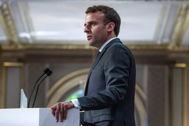 French President Emmanuel Macron addresses Paris Firefighters' brigade and security forces who took part at the fire extinguishing operations of the Notre Dame of Paris Cathedral fire, at the Elysee Palace in Paris, Thursday, April 18, 2019. (Christophe Petit Tesson, Pool via AP)