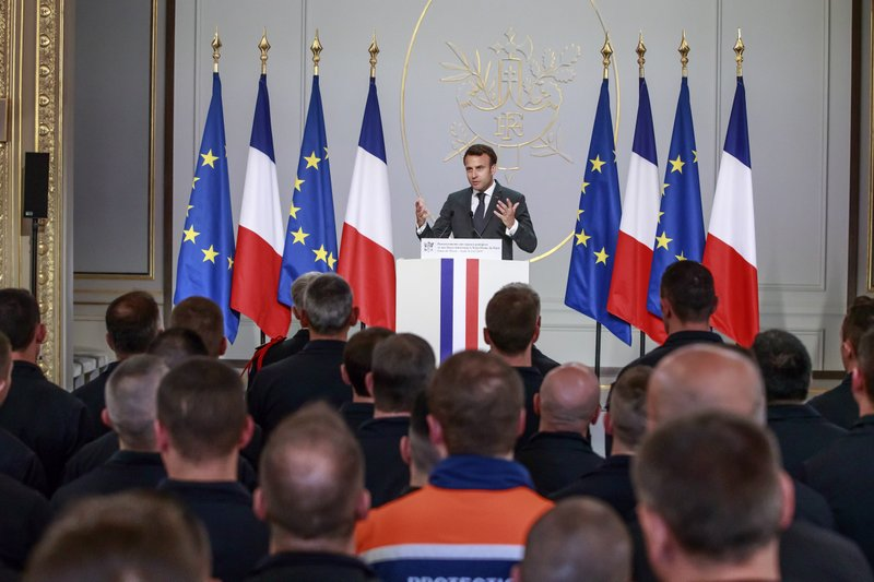 French President Emmanuel Macron, center, delivers a speech to Paris Firefighters' brigade and security forces who took part at the fire extinguishing operations of the Notre Dame of Paris Cathedral fire, at the Elysee Palace in Paris, Thursday, April 18, 2019. (Christophe Petit Tesson, Pool via AP)