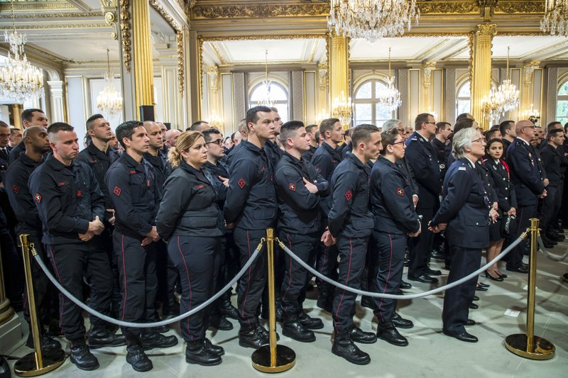 Paris Firefighters' brigade and security forces who took part to the fire extinguishing operations of the Notre Dame of Paris Cathedral listen to French President Emmanuel Macron at the Elysee Palace in Paris, Thursday, April 18, 2019. (Christophe Petit Tesson, Pool via AP)
