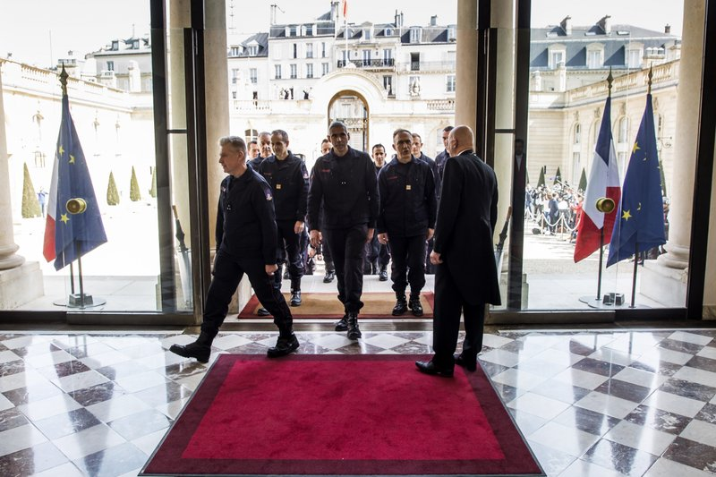 Firefighters and security forces who took part to the fire extinguishing operations at Notre Dame of Paris Cathedral, arrive for a ceremony at the Elysee Palace in Paris, Thursday, April 18, 2019. (Christophe Petit Tesson, Pool via AP)