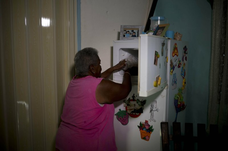Pura Castell puts in her freezer the three pieces of chicken she received from a government-run Bodega store, as part of her monthly quota of government-distributed food, after failing to find chicken the previous day in Bauta, Cuba, Friday, April 12, 2019. (AP Photo/Ramon Espinosa)