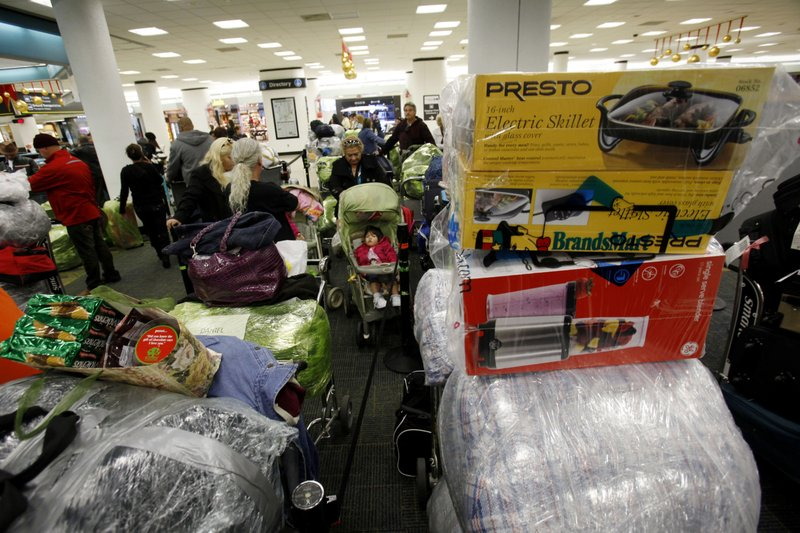 FILE - In this Dec. 16, 2010 FILE photo, carts are loaded with luggage as passengers wait in line for a flight to Cuba at Miami International Airport in Miami, ahead of the Christmas holiday. (AP Photo/Lynne Sladky, File)