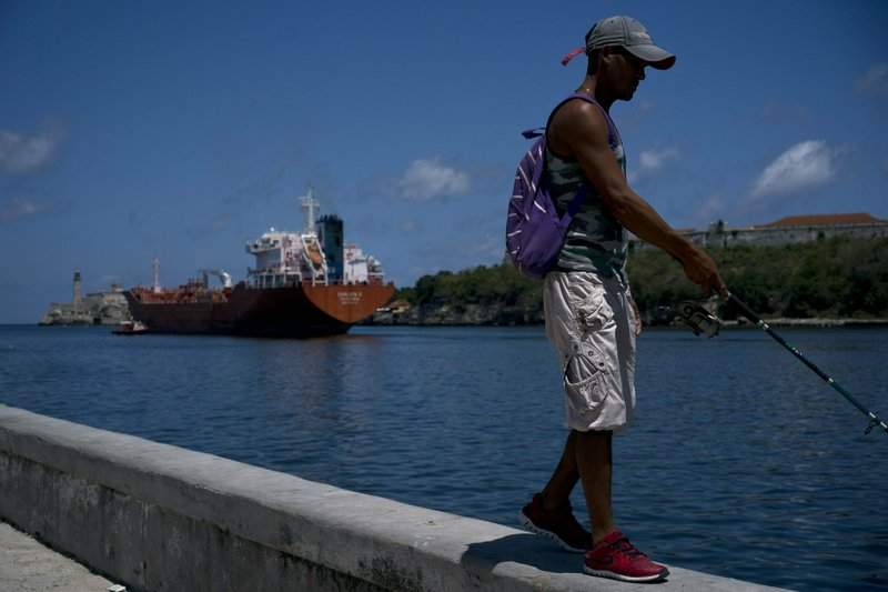 A fisherman walks on the Malecon seawall where an oil tanker can be see in the background in Havana, Cuba, Wednesday, April 17, 2019. (AP Photo/Ramon Espinosa)