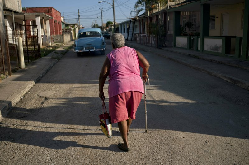 Pura Castell walks to a government-run butcher shop to buy chicken, after failing to find chicken the previous day in Bauta, Cuba, Friday, April 12, 2019. (AP Photo/Ramon Espinosa)