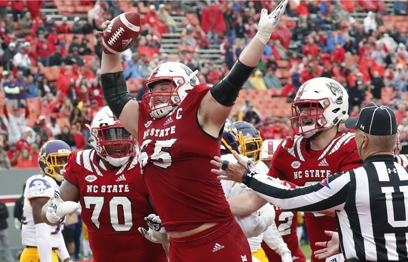 FILE - In this Dec. 1, 2018, file photo, North Carolina State's Garrett Bradbury (65) celebrates after he scored a touchdown during the second half of NCAA college football game, in Raleigh, N. (AP Photo/Chris Seward, File)
