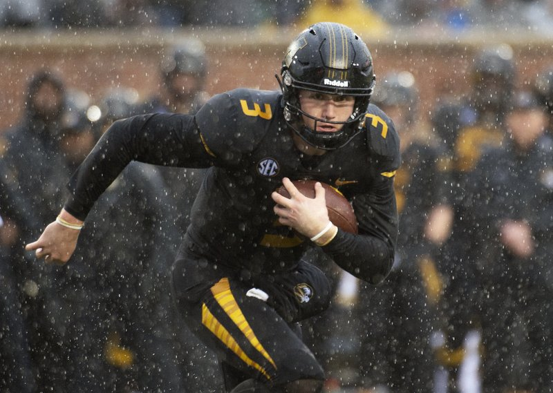 FILE - In this Nov. 23, 2018, file photo, Missouri quarterback Drew Lock runs with the ball during the first half of an NCAA college football game against Arkansas, in Columbia, Mo. (AP Photo/L.G. Patterson, File)