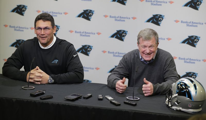 Carolina Panthers head coach Ron Rivera, left, and general manager Marty Hurney, right, share a laugh as they speak to the media in Charlotte, N. (AP Photo/Chuck Burton)