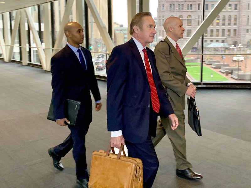 Former Minneapolis police officer Mohamed Noor, left, arrived with his defense attorneys Peter Wold, center, and Thomas Plunkett, right, on April 17, 2019, before another day of testimony in Noor's murder and manslaughter trial in Minneapolis. (AP Photo/Jeff Baenen)