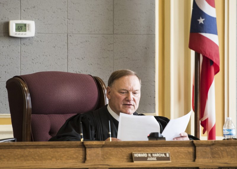 In this Wednesday, April 17, 2019 photo, Scioto County Court of Common Pleas Judge Howard Harcha reads the recently signed documents by Casey Pigge regarding Pigge's guilty plea in Chillicothe, Ohio. (Robert McGraw/The Chillicothe Gazette via AP)
